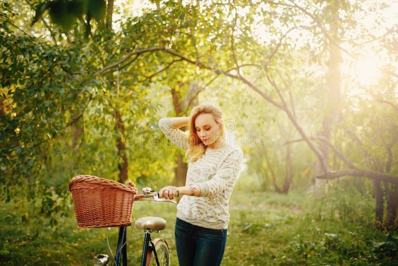 Blonde Schönheit auf einem Weinlesefahrrad stockfotos