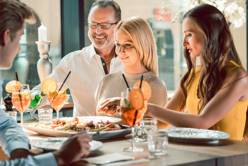 Blonde Schönheit, die mit ihren besten Freunden an einem modischen Restaurant zu Mittag isst stockbilder