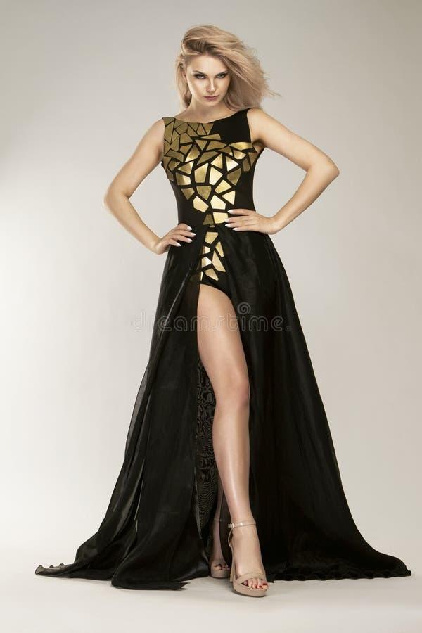 Blonde Schönheit im herrlichen modernen schwarzen langen Abendkleid, stockfoto