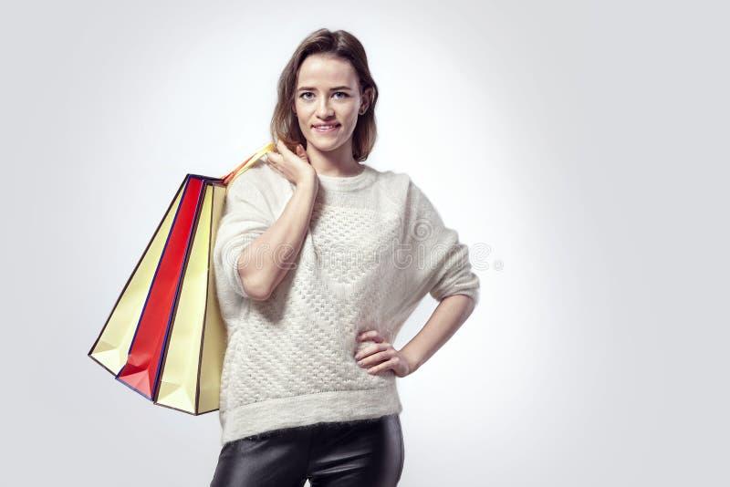 Blonde Schönheit mit Einkaufspapiertüten auf Schulter Ruhige Gefühle, kaukasisches Gesicht, Strickjacke stockbilder