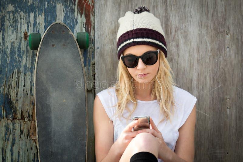 Blonde Schlittschuhläufer-Mädchen-Versenden von SMS-Nachrichten lizenzfreie stockbilder