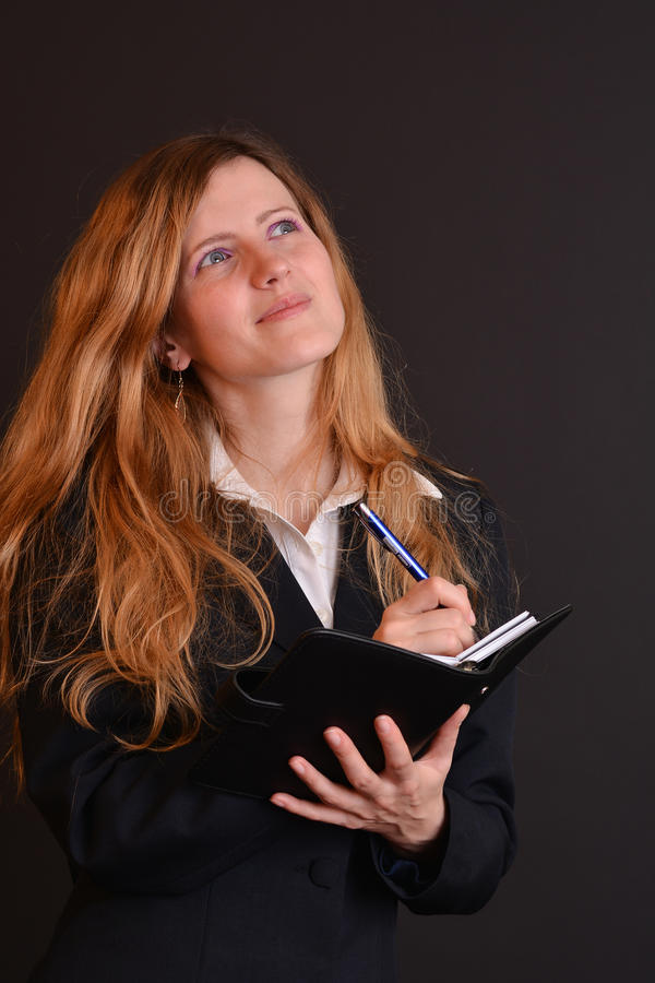 Blonde school director. Serious blonde school director, writing in her agenda with a pen, smiling and looking up, dressed in black office suite royalty free stock image