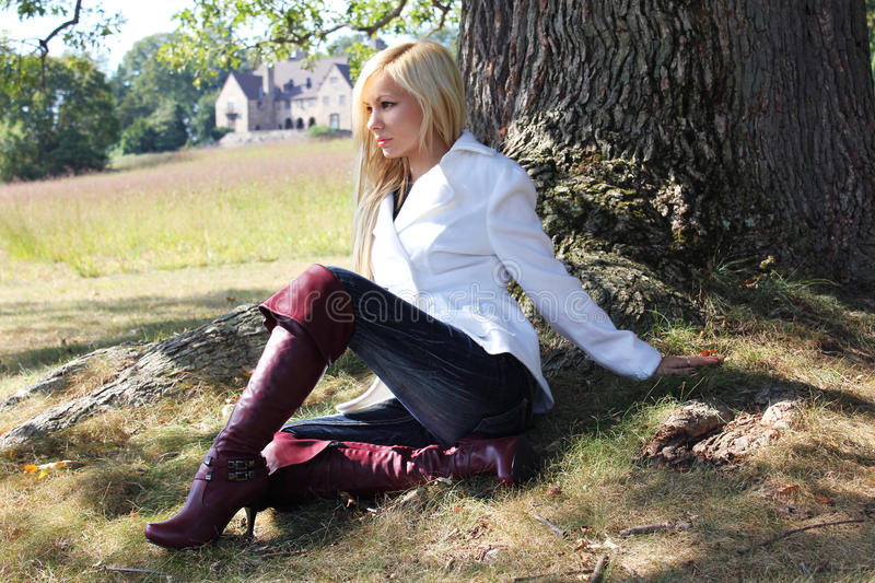 Blonde in boots. Beautiful blonde girl in burgundy boots sitting under a tree royalty free stock photo