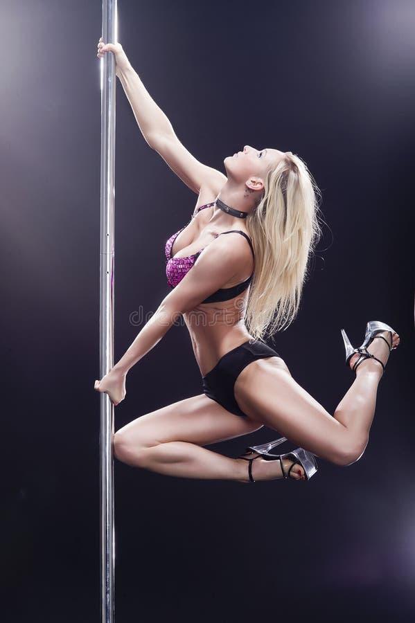 Blonde pole dance woman. Young pole dance woman in smoke stock image