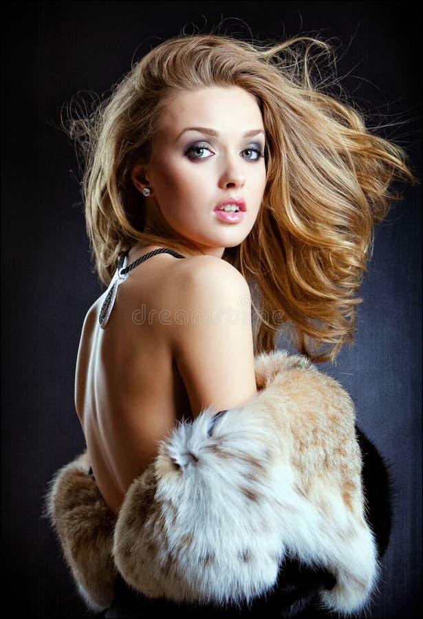 Blonde sexy sensuelle de fille dans un moitié-plan rapproché de manteau de fourrure photographie stock