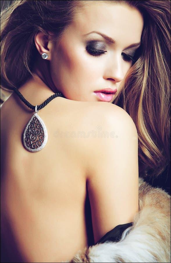 Blonde sexy sensuelle de fille dans une moitié du plan rapproché de manteau de fourrure avec photo stock
