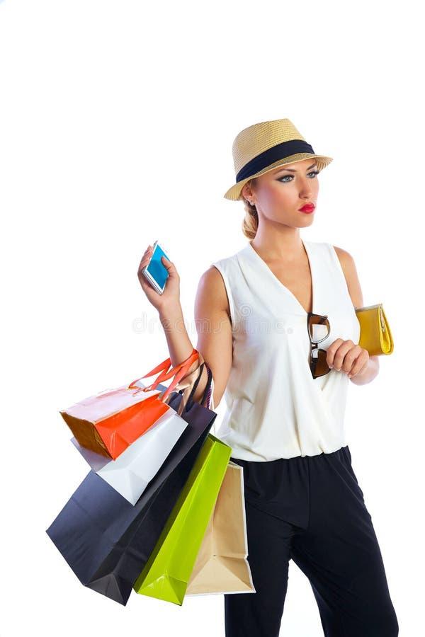 Blonde shopaholic vrouwenzakken en smartphone stock foto