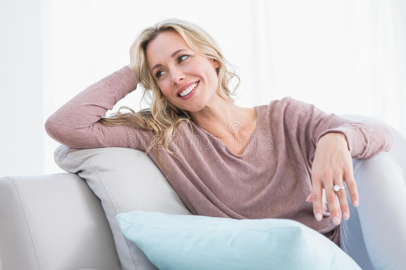 Blonde sitting on couch smiling and thinking. At home in the living room royalty free stock image