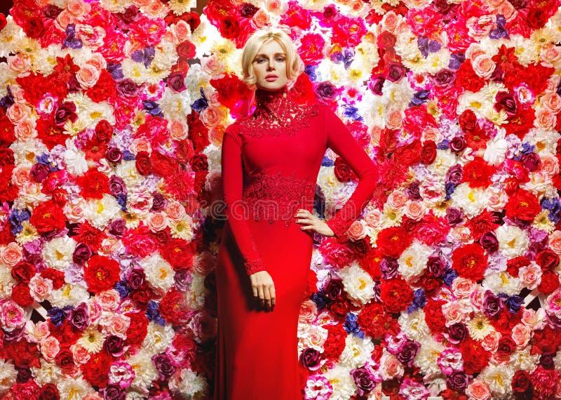 Blonde slanke vrouw over de bloemmuur royalty-vrije stock afbeelding