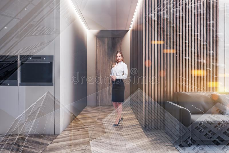 Woman in modern living room and kitchen. Blonde smiling businesswoman standing in modern studio apartment with soft gray sofa on the carpet and kitchen area with royalty free stock photography