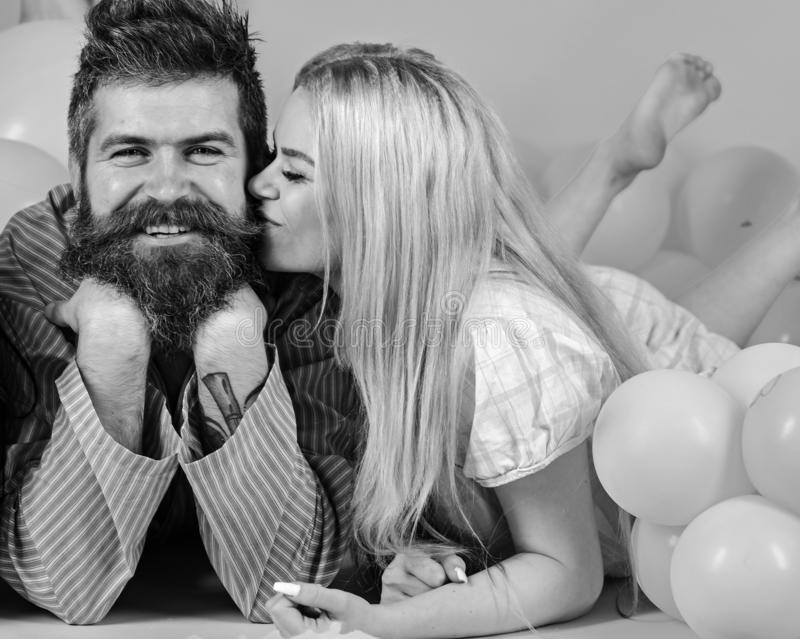 Blonde on smiling face kissing bearded macho, fall in love. Love concept. Couple in love in pajamas at girlish bedroom stock image