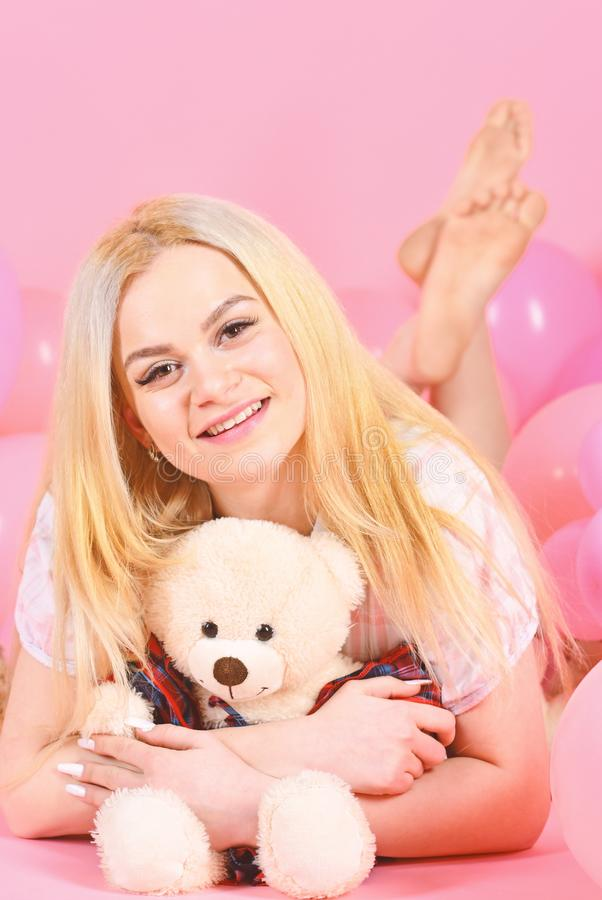 Blonde on smiling face relaxing with teddy bear toy. Birthday girl concept. Woman cute celebrate birthday with balloons. Girl in pajama, domestic clothes lay stock photography