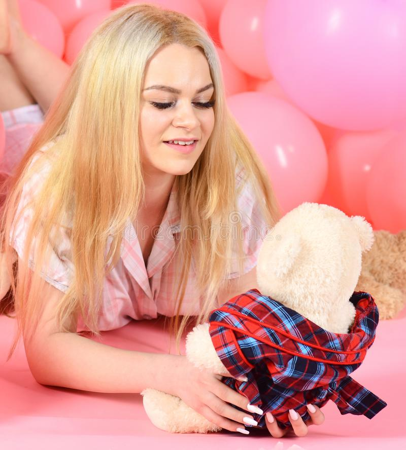 Blonde on smiling face relaxing with teddy bear toy. Girl in pajama, domestic clothes lay near air balloons, pink royalty free stock image