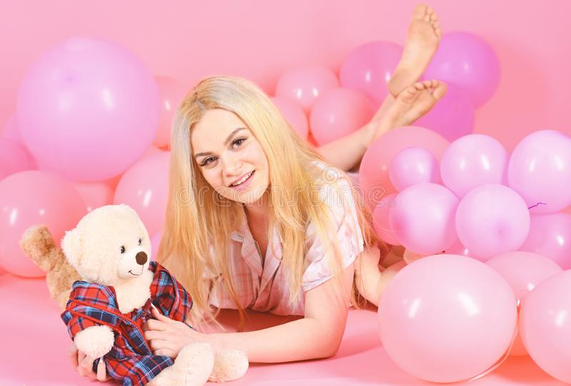 Blonde on smiling face relaxing with teddy bear toy. Girl in pajama, domestic clothes lay near air balloons, pink. Background. Birthday girl concept. Woman cute royalty free stock photos