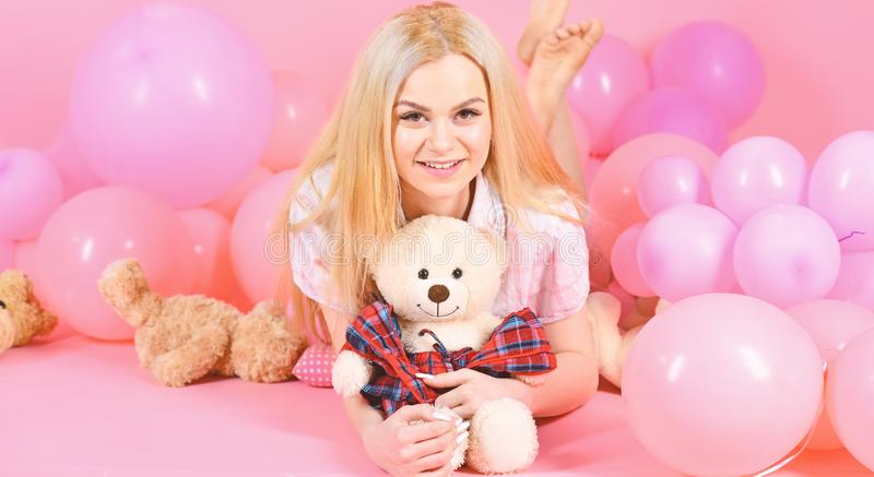 Blonde on smiling face relaxing with teddy bear toy. Woman cute celebrate birthday with balloons. Girl in pajama. Domestic clothes lay near air balloons, pink royalty free stock photo