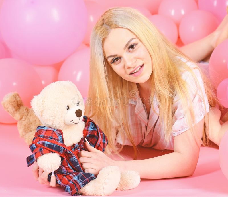 Blonde on smiling face relaxing with teddy bear toy. Woman cute celebrate birthday with balloons. Girl in pajama. Domestilothes lay near air balloons, pink royalty free stock photos