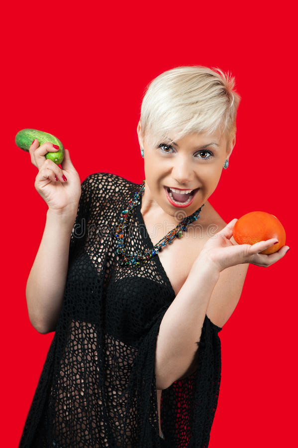 Blonde smiling and holding cucumber and tomato stock image