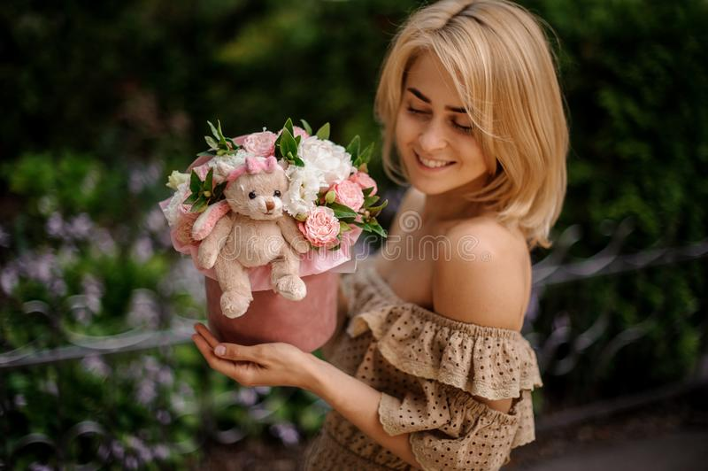 Blonde smiling woman holding a box filled with flowers stock image