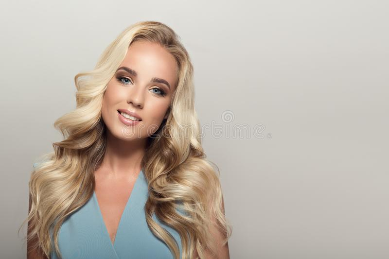 Blonde smiling woman with curly beautiful hair. Blonde smiling woman with long curly beautiful hair royalty free stock photos
