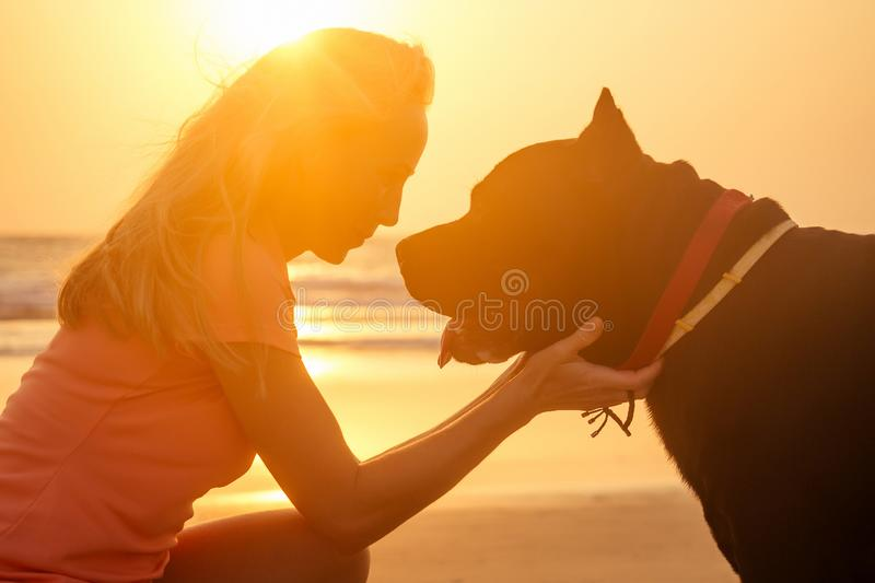 Blonde smiling young woman hugging her Cane Corso dog on the beach.  royalty free stock photography
