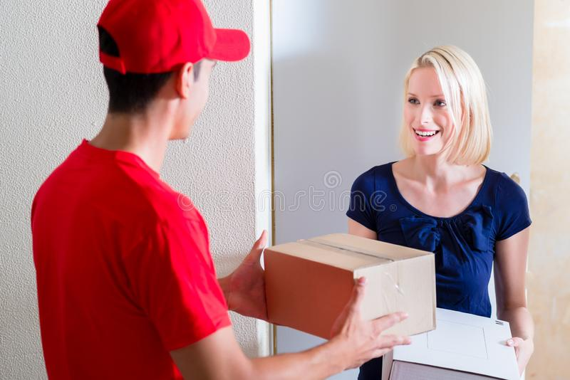 Young woman receiving the boxes from delivery man stock images