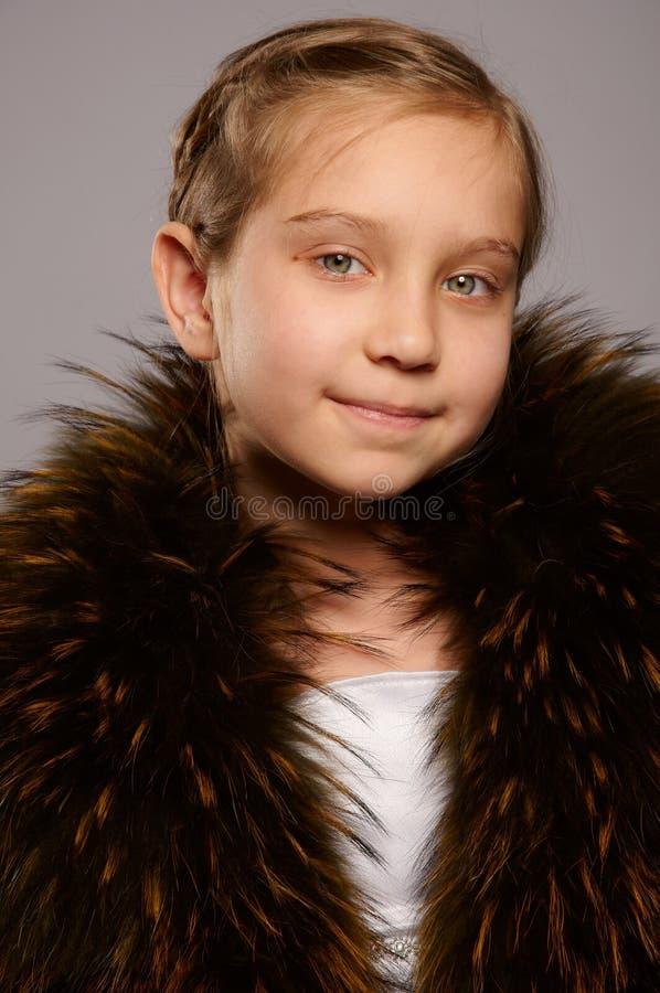 Blonde sorridente della ragazza in cappotto di pelliccia fotografia stock libera da diritti