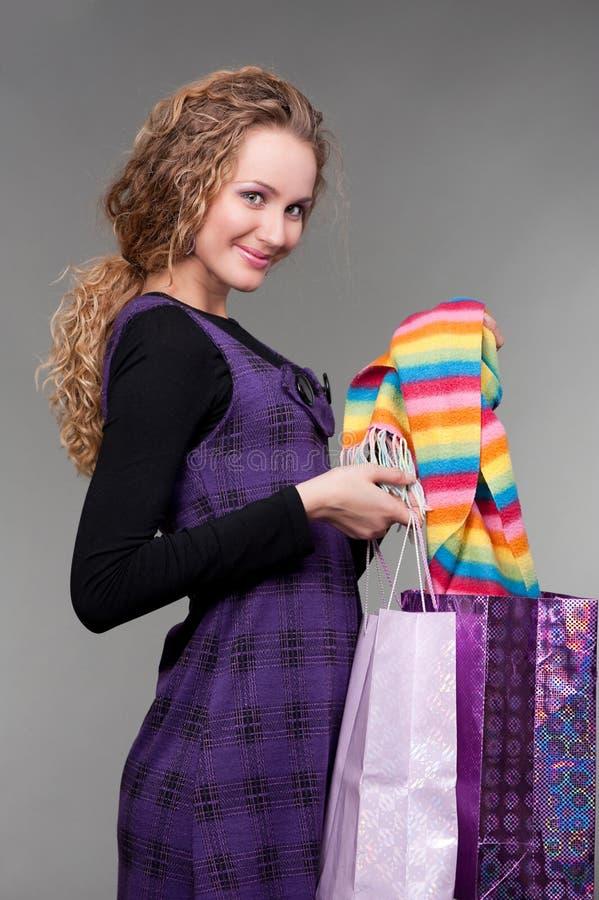 Blonde souriante lui affichant des achats image stock