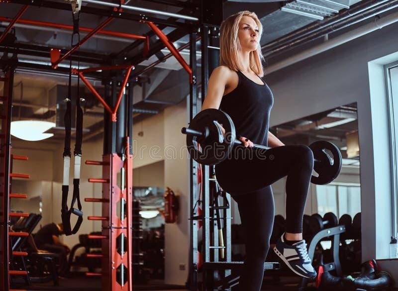 Blonde sportief wijfje in sportkleding die oefening met een barbell in een een geschiktheidsclub of gymnastiek doen royalty-vrije stock foto
