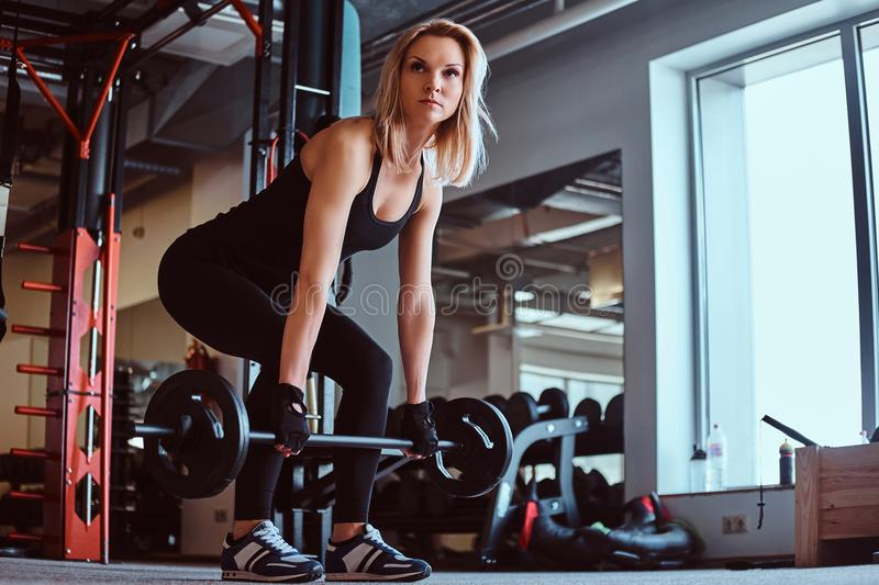 Blonde sportive female in sportswear doing deadlift with barbell in the fitness club or gym. stock images