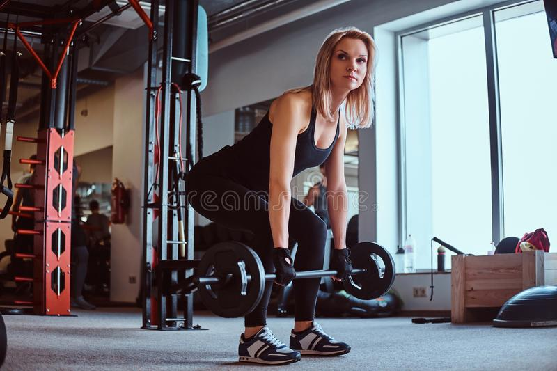 Blonde sportive female in sportswear doing deadlift with barbell in the fitness club or gym. royalty free stock photo