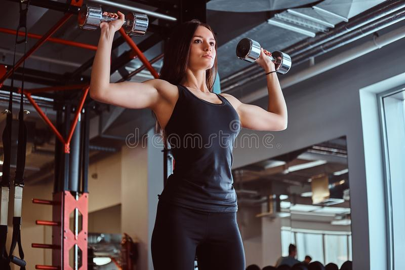 Blonde sportive female in sportswear doing exercise on shoulders with dumbbells in the fitness club or gym. stock image