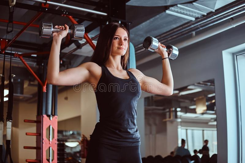 Blonde sportive female in sportswear doing exercise on shoulders with dumbbells in the fitness club or gym. stock photography