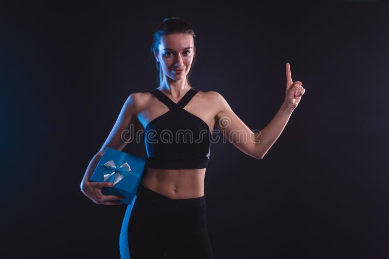 Blonde sportive tenant un boîte-cadeau bleu photographie stock libre de droits