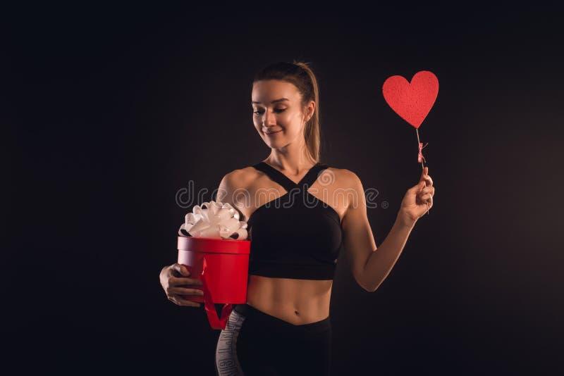 Blonde sportive tenant un coeur et un boîte-cadeau photographie stock