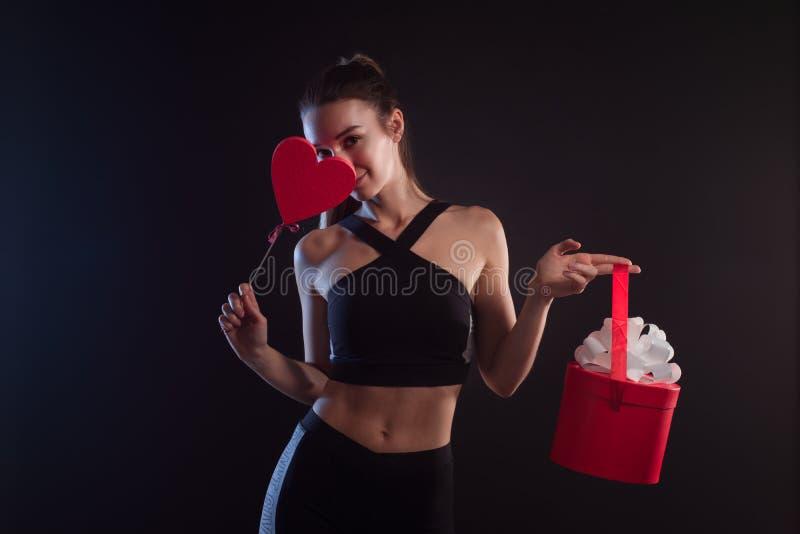 Blonde sportive tenant un coeur et un boîte-cadeau image libre de droits