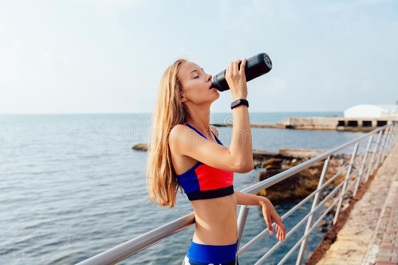 Blonde sportswoman drinking a water after training outdoors royalty free stock photography