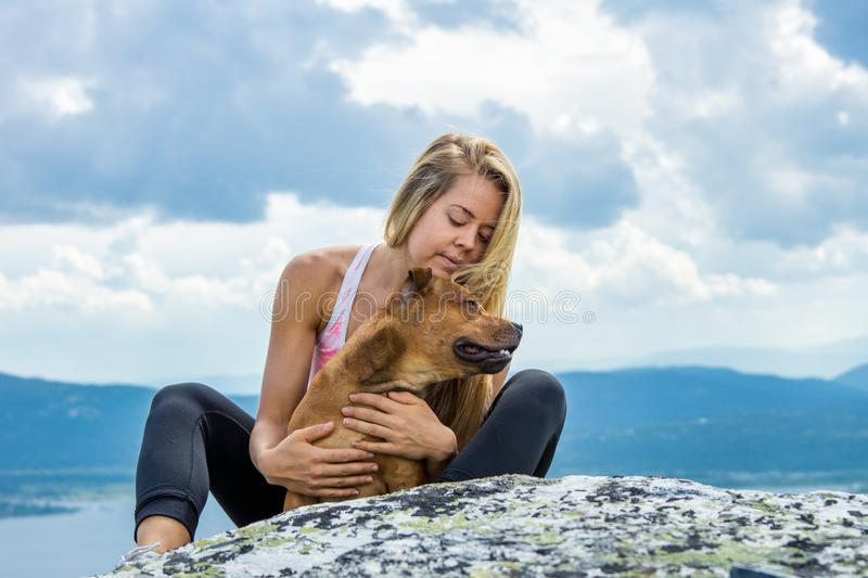 Blonde sporty girl and her pet are cuddling outdoors in beautiful mountain scenery during hike. Healthy and lifestyle concept stock photo