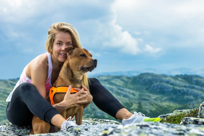 Blonde sporty girl and her pet are cuddling outdoors in beautiful mountain scenery during hike. Healthy and lifestyle concept royalty free stock image