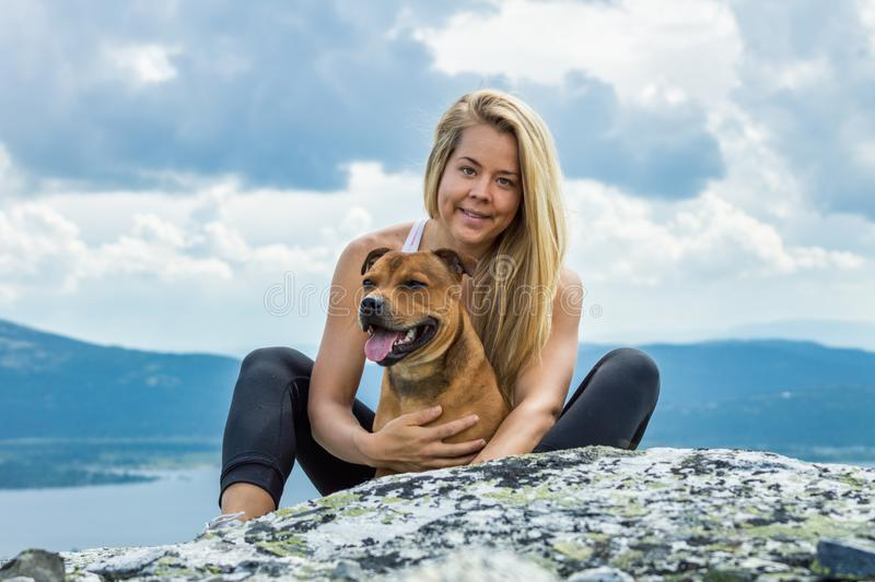 Blonde sporty girl and her pet are cuddling outdoors in beautiful mountain scenery during hike. Healthy and lifestyle concept royalty free stock photo
