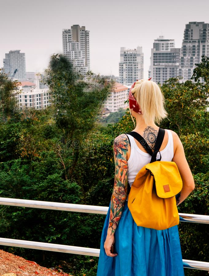 The blonde stands with his back to the camera, looking at the city from a high point. Wearing white jersey, blue skirt. Orange backpack. Hands with tattoos stock photos