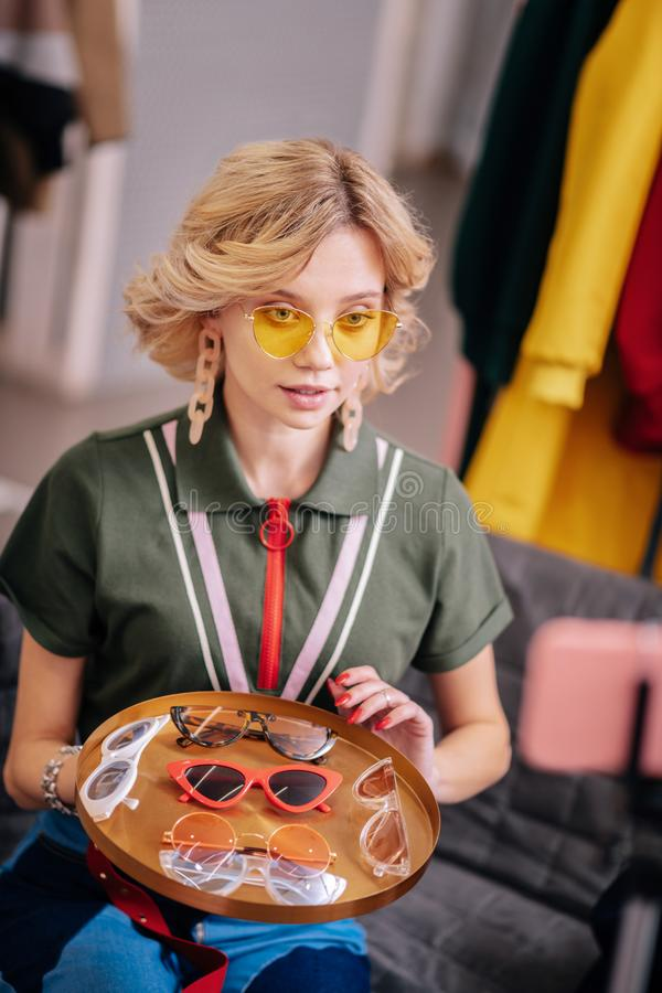 Blonde stylist with short wavy hair filming blog about sunglasses stock image