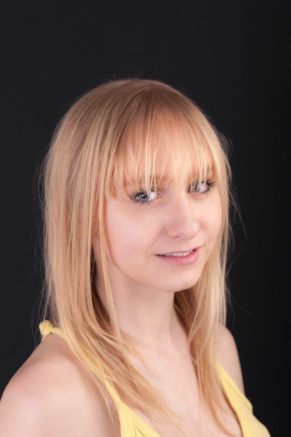 Blonde su una priorità bassa nera fotografia stock