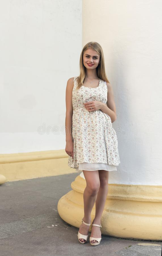 Blonde in a summer white dress. Blonde in a summer short white dress stock image