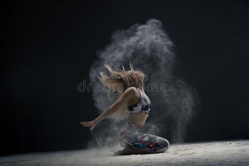 Blonde sur la vue de plancher dans un nuage de poussière blanc image libre de droits