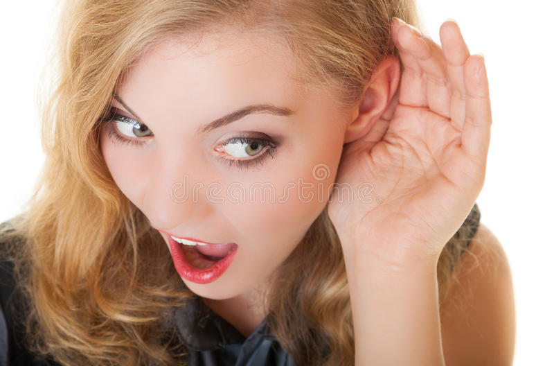 Blonde surprised gossip girl with hand behind ear listening secret stock photos