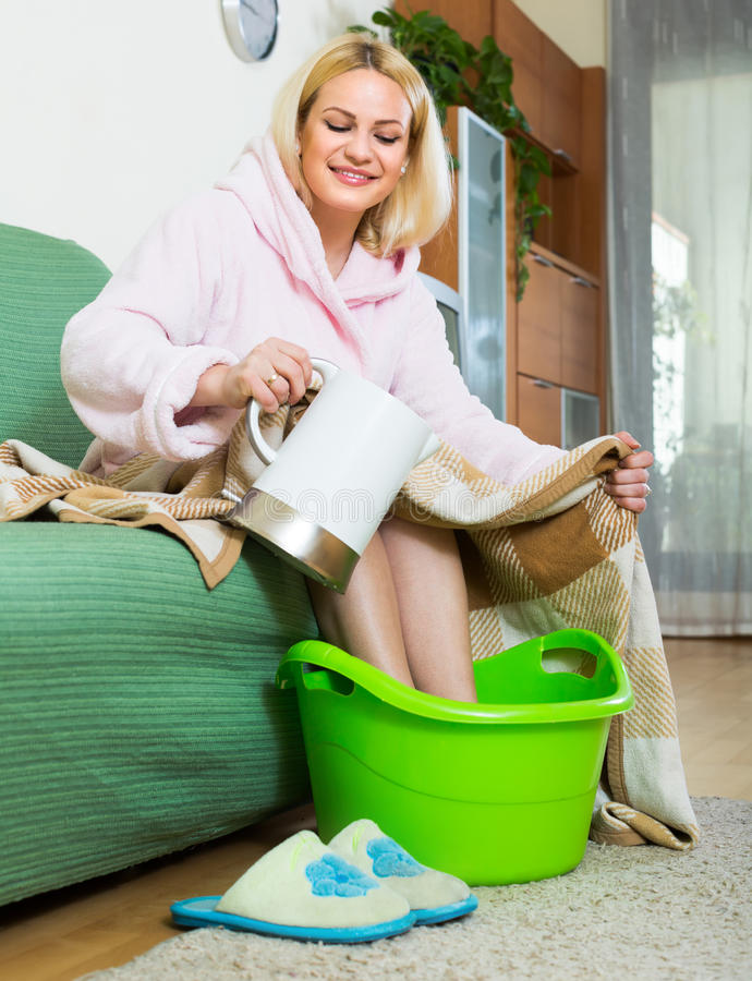 Blonde taking foot bath at home royalty free stock photos