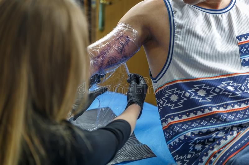 A blonde tattooist is covering a tattoo on a the arm of a boy. In her small studio stock photography