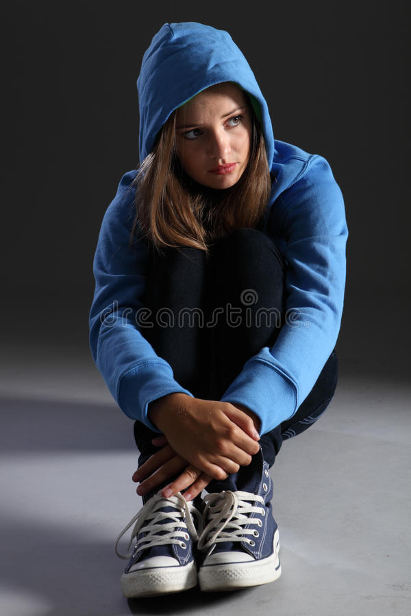 Blonde teenager girl alone and sad in blue hoodie royalty free stock photography