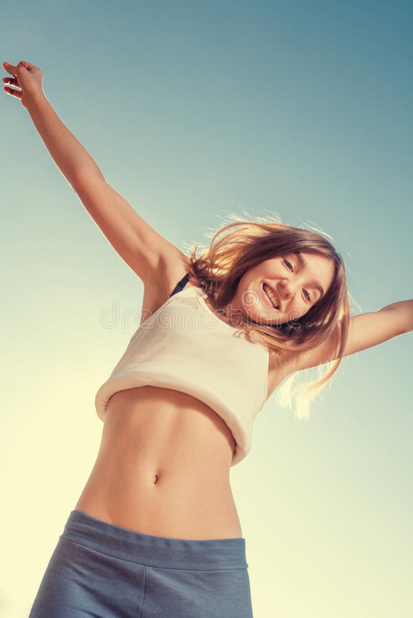 Blonde teenager girl jumping happy with the blue. Free and happy women. Blonde teenager female jumping with the blue sky in the background stock images