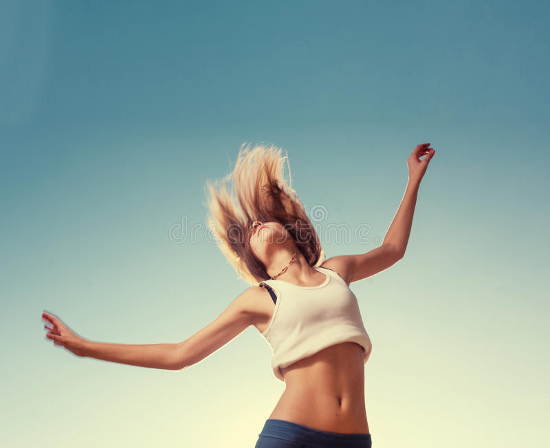 Blonde teenager girl jumping happy with the blue royalty free stock photography